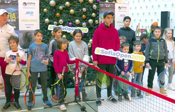 Адриан Андреев игра тенис с десетки деца под голяма коледна елха